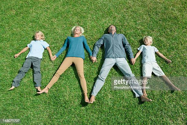Family with two children lying side by side hand in hand on lawn, high angle view
