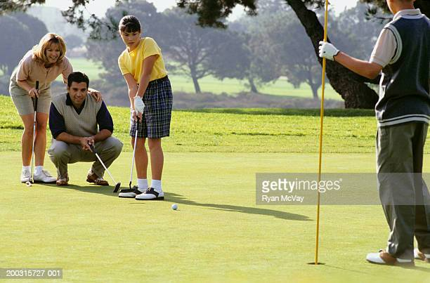 Family with two children (12-13), (16-17), on putting green at golf course