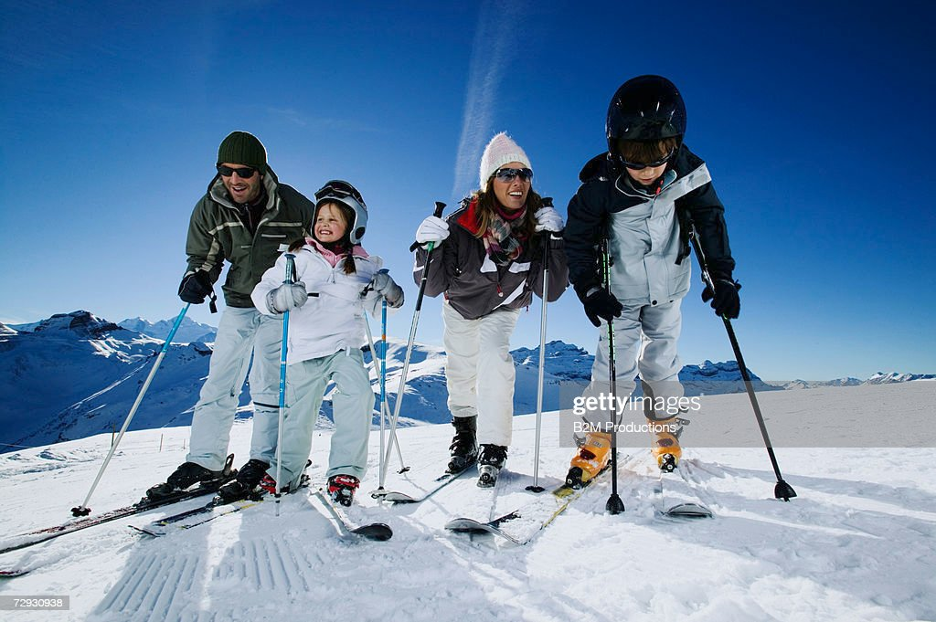 Family with two children (6-8) on ski slope : Stock Photo