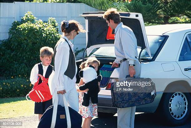 Family with two children (5-8) packing bags and toys into car