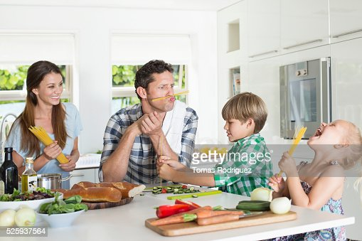 Family with two children (4-5 ,6-7) playing in kitchen : Bildbanksbilder