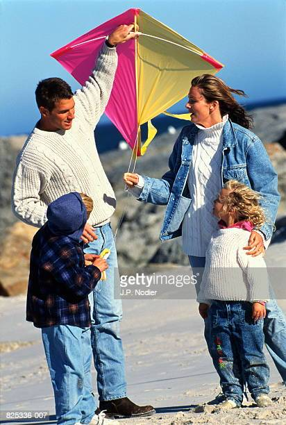 Family with two children (6-8) playing with kite on beach