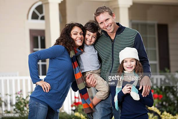 Family with two children standing in front of house