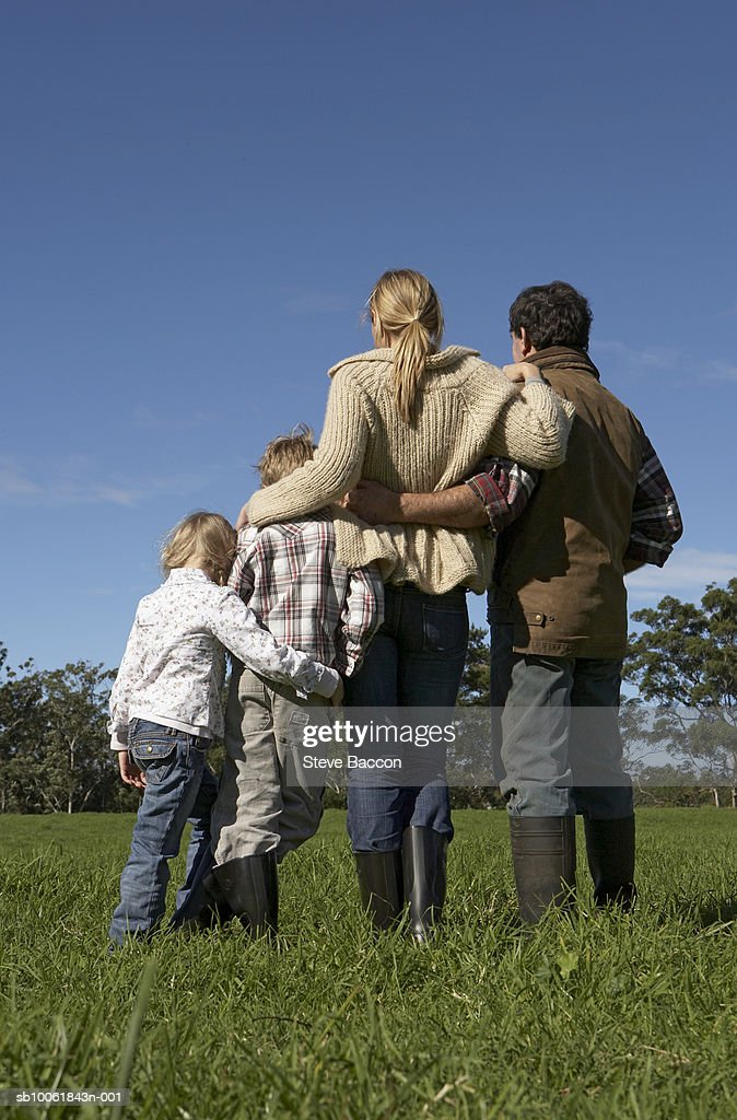 Family with two children (6-9) standing on meadow, rear view : Stock Photo