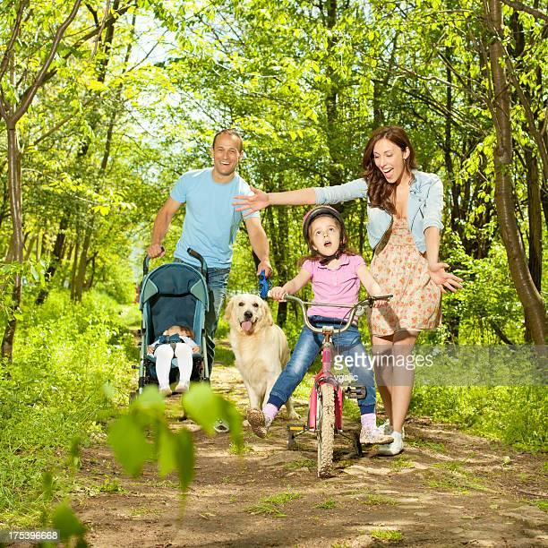 Familie mit zwei Kindern Wandern und Radfahren im Wald.