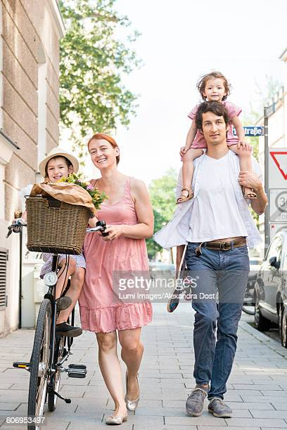 Family with two children walking in city