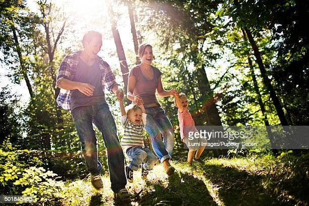 Family with two children walking in forest, having fun, Bavaria, Germany