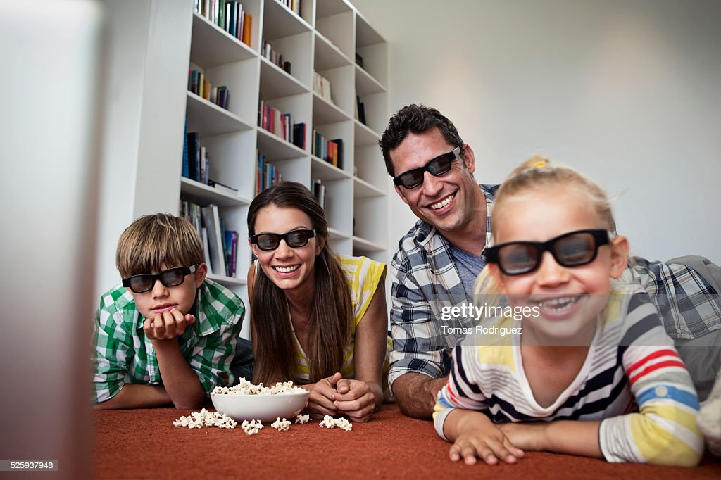 Family with two children (4-5 ,6-7) watching tv on floor : Stock Photo