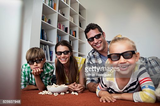 Family with two children (4-5 ,6-7) watching tv on floor : Stockfoto
