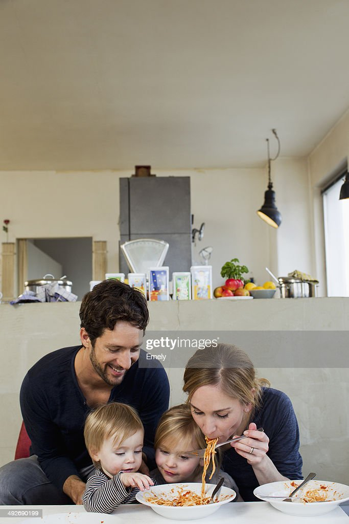Family with two daughters eating spaghetti meal