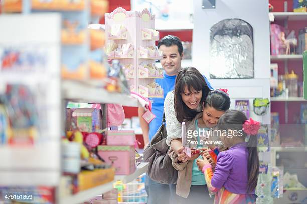 Family with two daughters shopping in toy shop