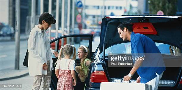 Family with two daughters (6-8) unloading car in urban street