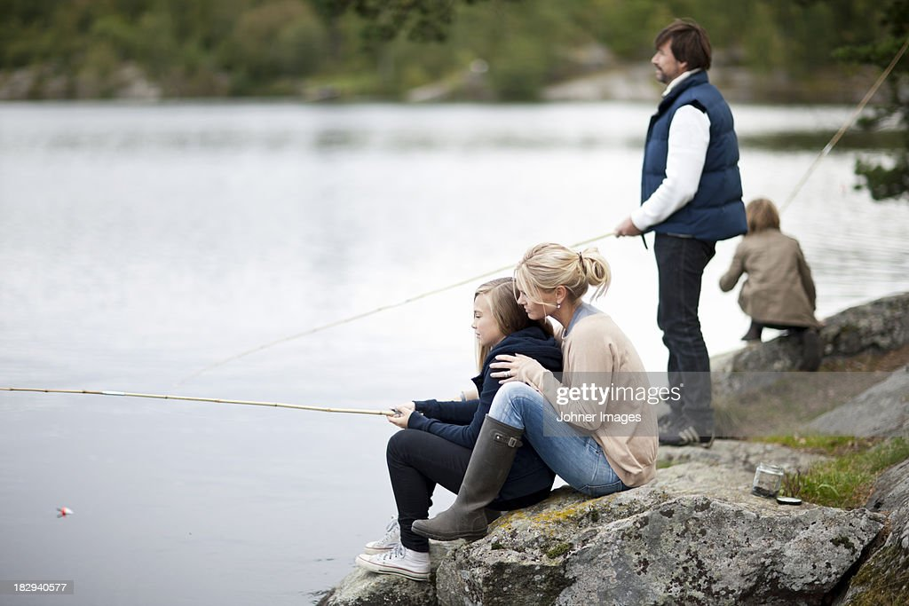 Family with two kids fishing at lake
