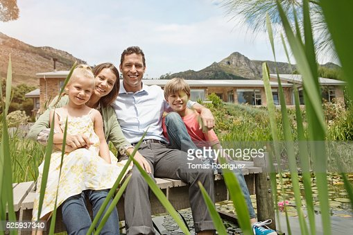 Family with two kids (4-5, 10-12) sitting on jetty : Stockfoto