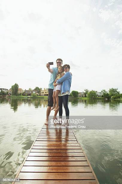 Family with young daughter standing together at end of lake pier taking selfie