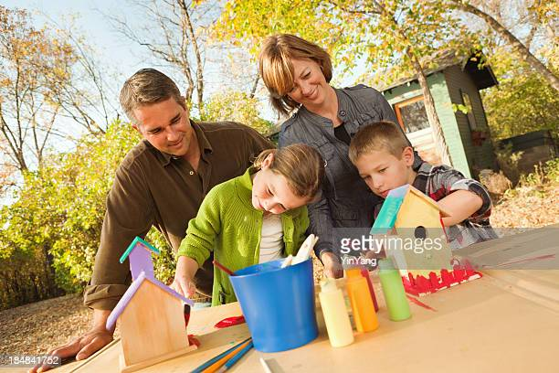 Family Working Together on a Birdhouse Painting Project Hz