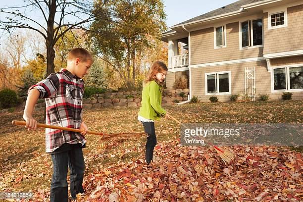 Family Working Together Raking Fall Leaves at Backyard of Home