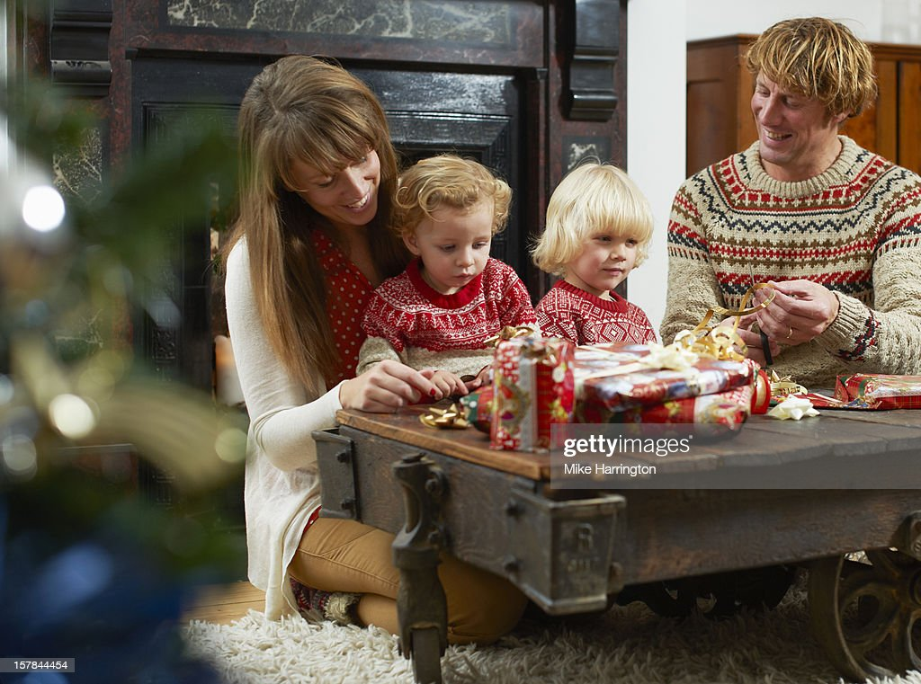 Family wrapping Christmas presents in living room. : Stock Photo