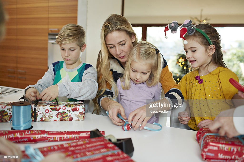 Family wrapping up christmas presents : Stock Photo