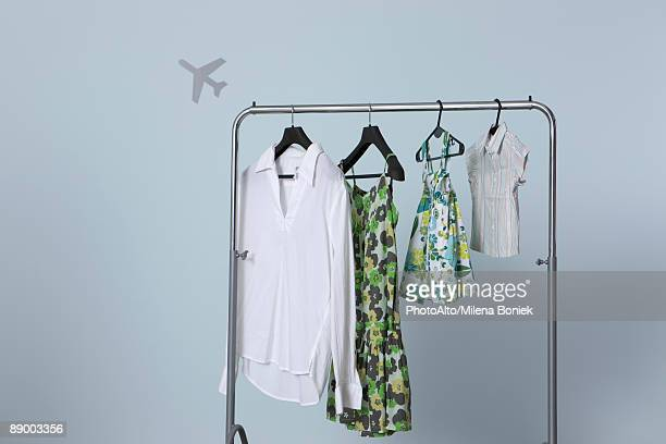 Family's summer clothing hanging on clothes rack, airplane shape in background
