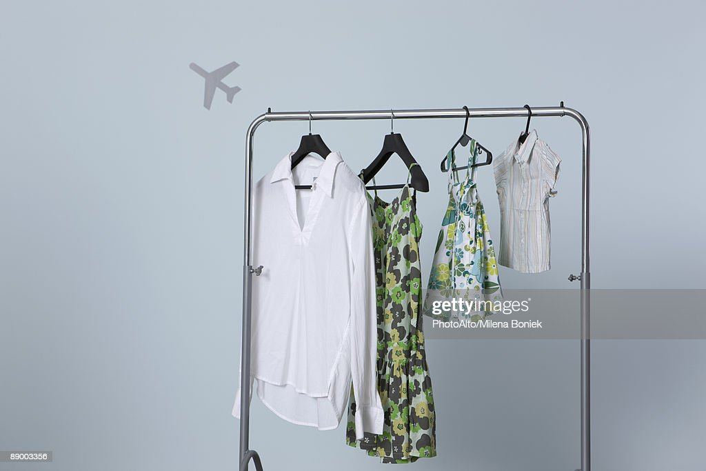 summer clothing hanging on clothes rack airplane shape in background - Clothes Hanger Rack