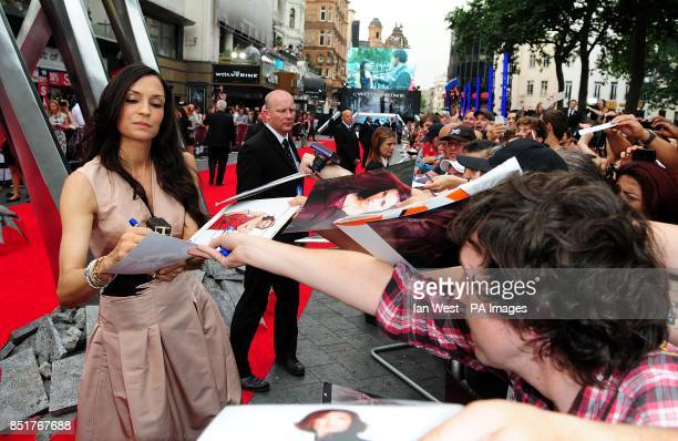 Famke Janssen signs autographs for fans whilst arriving for the UK Premiere of The Wolverine at the Empire Leicester Square London