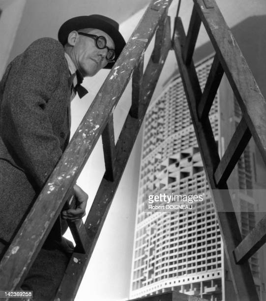Famous architect Le Corbusier on a ladder in front of a scale model of one of his project for Marine district of Algiers France in 1945