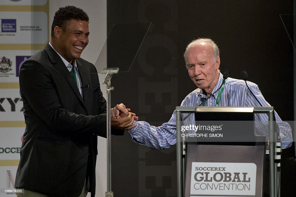Famous Brazilian former football star Ronaldo Nazario (C), thanks ex football player and coach Mario Jorge Lobo Zagallo after receiving from him a trophy for his career during the opening of the Soccerex football convention, in Rio de Janeiro, Brazil, on November 14, 2012. Soccerex is the leading event provider for the global football industry. AFP PHOTO/Christophe Simon