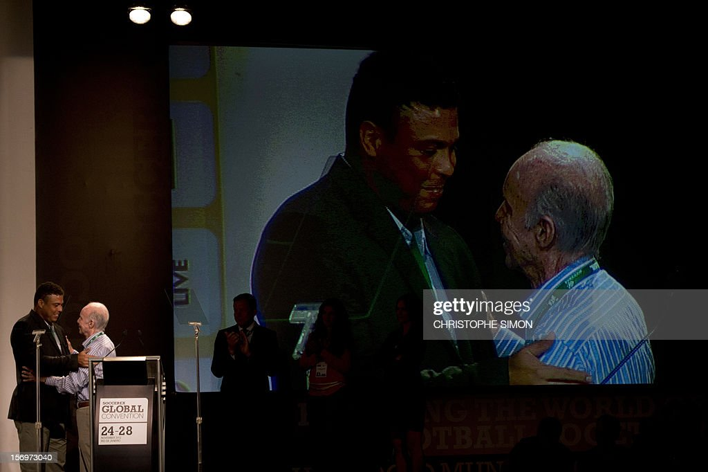 Famous Brazilian former football star Ronaldo Nazario (L), thanks ex football player and coach Mario Jorge Lobo Zagallo after receiving from him a trophy for his career during the opening of the Soccerex football convention, in Rio de Janeiro, Brazil, on November 14, 2012. Soccerex is the leading event provider for the global football industry. AFP PHOTO/Christophe Simon