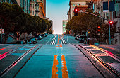 Low angle twilight view of an empty road with cable car tracks leading up a steep hill at famous California Street at dawn, San Francisco, California, USA