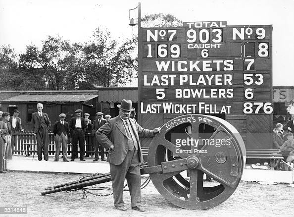 Famous cricket groundsman 'Bosser' Martin with his roller standing in front of a scoreboard displaying England's final score in the test match...