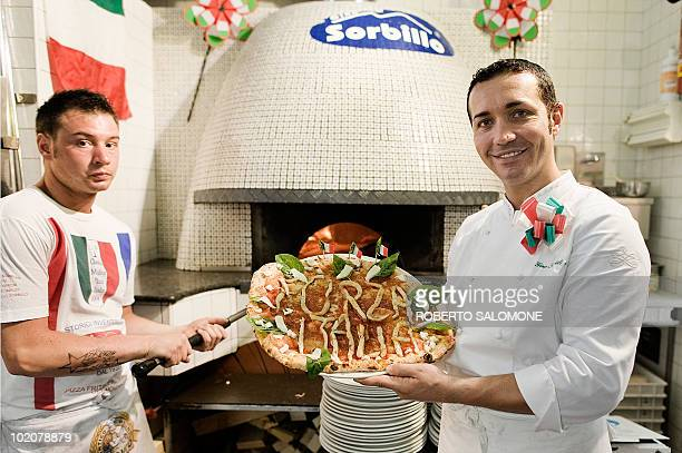 Famous napolitan pizza maker Gino Sorbillo shows the 'Forza Italia Pizza' he created for Italy's national football team debut against Paraguay at the...