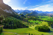 Famous Neuschwanstein Castle visible in the distance, located on a rugged hill above the village of Hohenschwangau near Füssen in southwest Bavaria, Germany