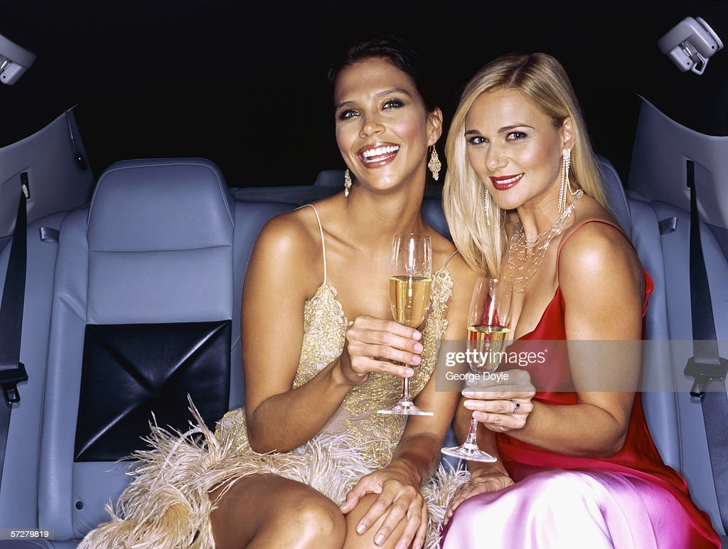 Famous, successful women celebrating in limousine : Stock Photo