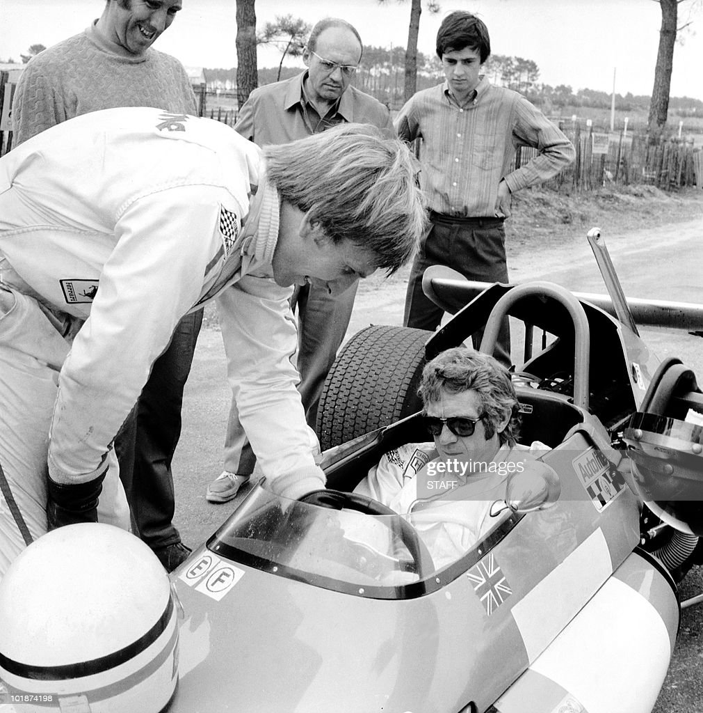 Famous US movie star Steve McQueen at the wheel of a Brabham F2 at Le Mans 18 July 1970 listens to British Formula 1 pilot Derek Bell who is giving...