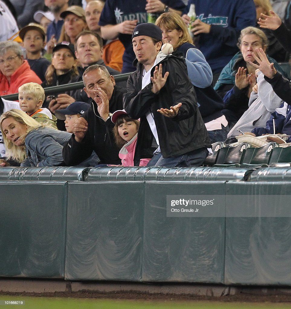 A fan along the first base side tries to catch a hard hit foul ball during the game between the Seattle Mariners and the Los Angeles Angels of...