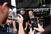 Fan Anthony Colletti gets his photo with driver Brittany Force during a rain delay at day one of the MoPar Mile High Nationals at Bandimere Speedway...
