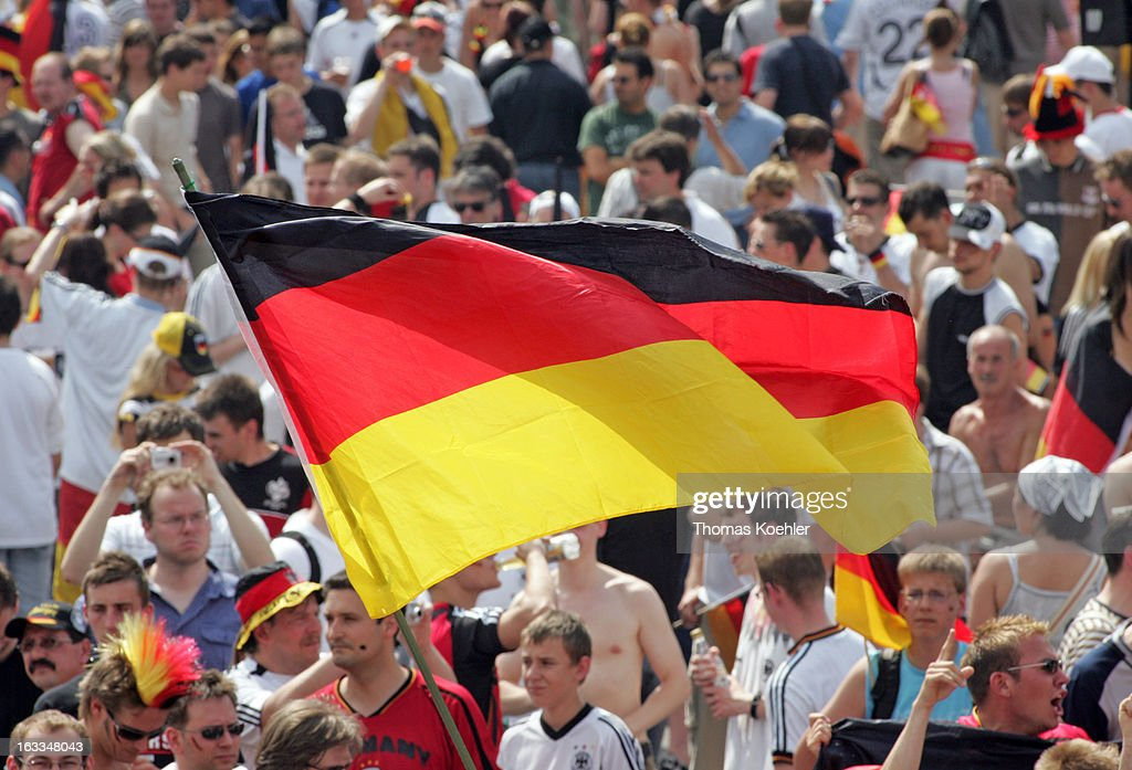 Fan area in Berlin during the FIFA World Cup 2006, International Soccer Tournament, Swinging a german flag, Fans in a crowd during a game of the German team, June 20, 2006, Berlin, Germany.