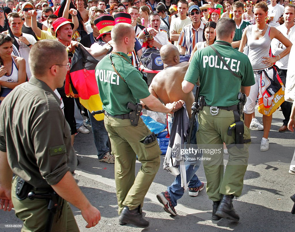 Fan area in Berlin during the FIFA World Cup 2006, International Soccer Tournament, Police officers are frogmarching somebody off, German Fans are watching disapprovingly, Game of the German Team, June 20, 2006, Berlin, Germany.