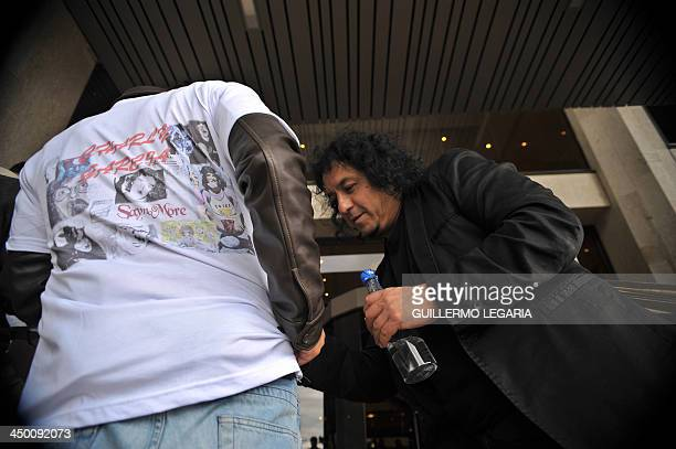 A fan asks Tono the drummer of Argentine musician Charly Garcia's band 'The Prostitution' for an autograph as he leaves a hotel in Bogota on November...
