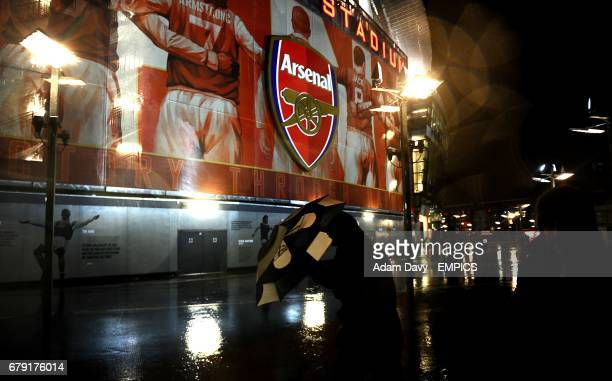 A fan attempts to shield under a umbrella as rain falls heavily around the Emirates Stadium before the match