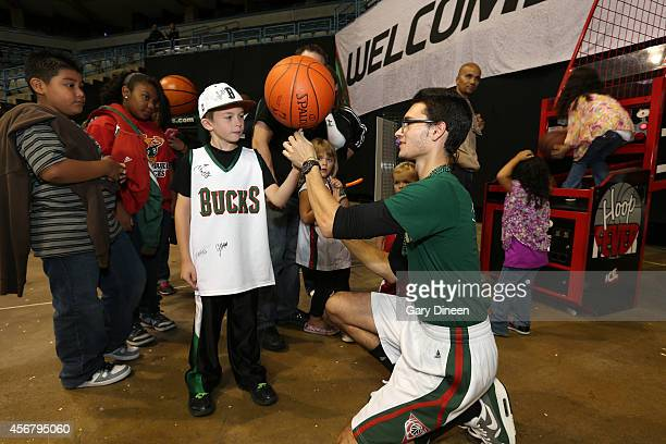 A fan attempts to spin a ball with the assistance of a member of the Milwaukee Bucks Hoop Troop during the 2014 Milwaukee Bucks Fan Fest and Open...
