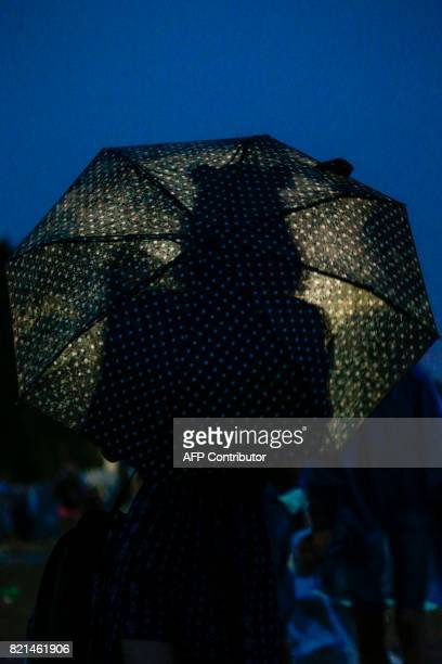 A fan attends a concert during the Lollapalooza music festival at the Longchamp Hippodrome in Paris on July 23 2017 / AFP PHOTO / GEOFFROY VAN DER...