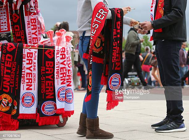 A fan buys a half and half scarf outside the ground prior to the Manchester United Foundation charity match between Manchester United Legends and...