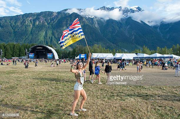 A fan carries a British Columbia flag at Pemberton Music Festival on July 17 2016 in Pemberton BC