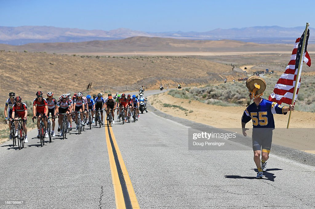 A fan carries an American Flag as he chases the breakaway early in Stage Three of the 2013 Amgen Tour of California from Palmdale to Santa Clarita on May 14, 2013 in Palmdale, California.