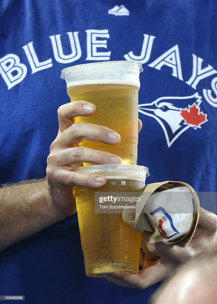 A fan carries beer and a hot dog during the Minnesota Twins MLB game against the Toronto Blue Jays on October 3, 2012 at Rogers Centre in Toronto, Ontario, Canada.