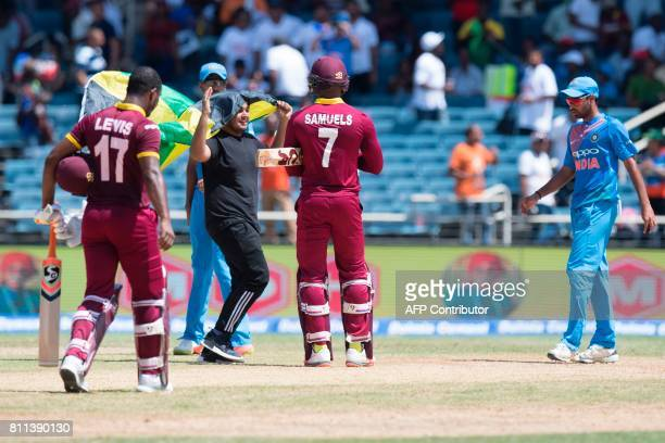 A fan carrying a Jamaican flag runs on the pitch as West Indies' Evin Lewis and Marlon Samuels celebrate winning the T20 match between West Indies...