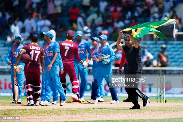 A fan carrying a Jamaican flag runs on the pitch as West Indies' Evin Lewis and Marlon Samuels shake hands with the Indian team after winning the T20...