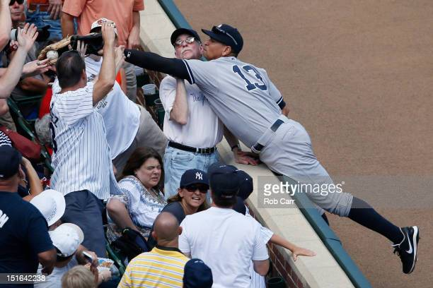 A fan catches a foul ball hit by Mark Reynolds of the Baltimore Orioles in front of third baseman Alex Rodriguez of the New York Yankees during the...